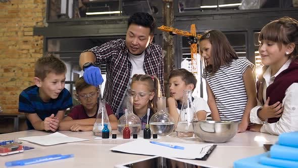 Six Young Children Working with Chemical Reaction in Chemistry Lab