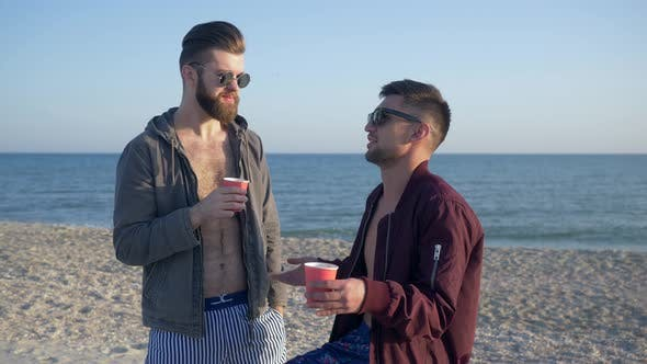 Thumbnail for Male Gossip, Cheerful Friends in Glasses Are Drinking Tea and Talking on Beach