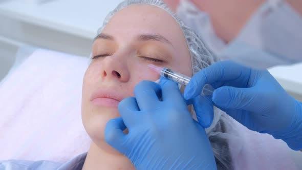 Kosmetikerin macht mehrere Injektionen Biorevitalisierung in Frau Gesichtshaut