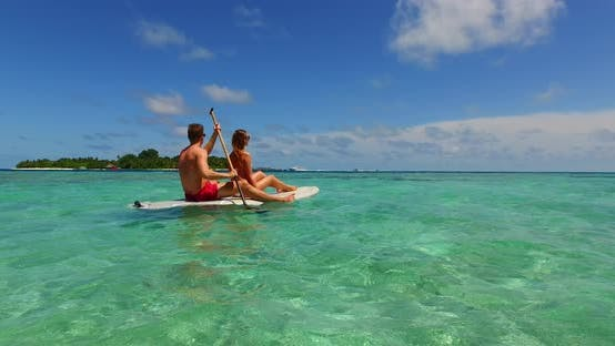 Romantic man and woman on romantic honeymoon spend quality time on beach on paradise white sand back