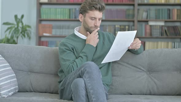 Thumbnail for Thoughtful Man Sitting on Sofa and Studying Documents