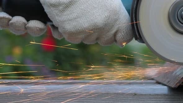 Worker in Gloves Use Angle Grinder