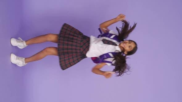 Счастливый Активный Индийская школьница Прыжки на фиолетовом фоне