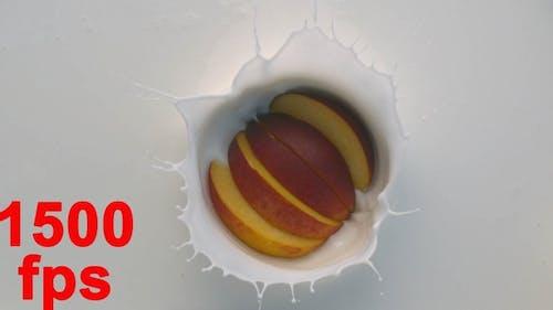 Slices Of Peach Fruit Falling Into White Yogurt With Splashes 4K