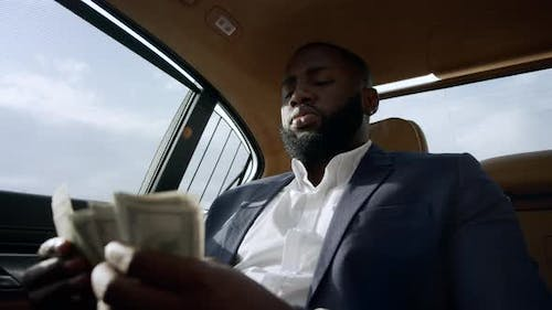Closeup African Man Counting Money at Car. Businessman Sitting with Money at Car