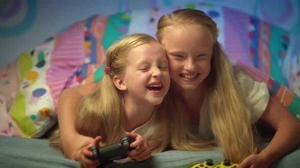 Joyful Blonde Kids Playing Video Game with Joystick