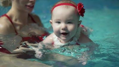 Baby Teaching to Swim in the Swimming Pool