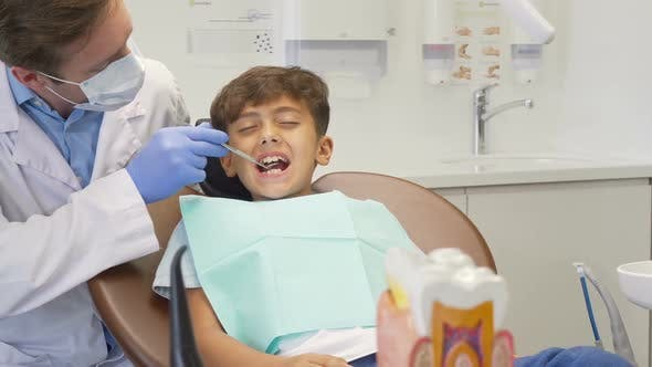 Thumbnail for Young Boy Looking Scared, Having His Teeth Examined By Mature Dentist