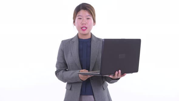 Thumbnail for Happy Young Asian Businesswoman Talking While Using Laptop