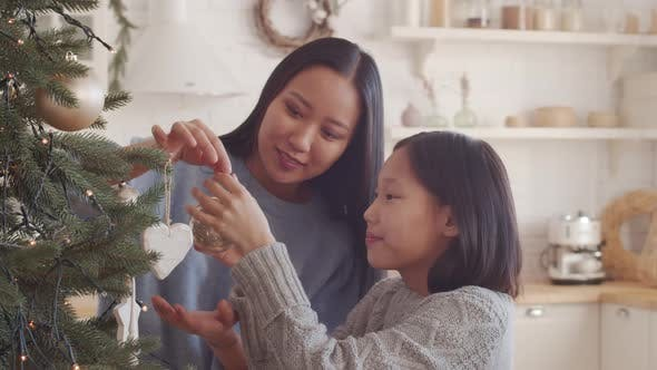 Joyous Asian Mother and Daughter Decorating Christmas Tree at Home