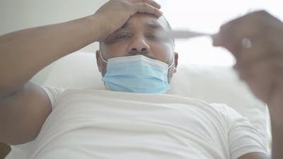 Close-up of Ill African American Man in Face Mask with Headache and Fever Looking at Thermometer
