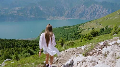 Tourist Girl Walks on the Rocky Mountain with Beautiful Landscape