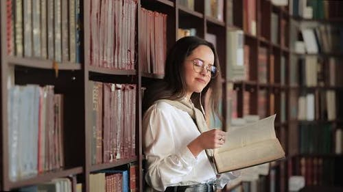 Smiling Girl in Library Near Bookshelf