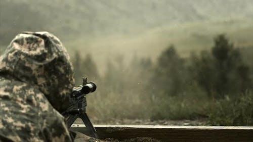 Super slow motion shot of soldier shooting chain gun; training at firing range.