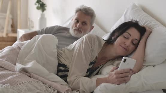 Thumbnail for Jealous Senior Caucasian Man Looking Over Shoulder of Wife at Smartphone Screen As Woman Messaging