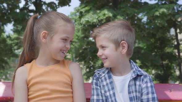 Thumbnail for Portrait of Cute Blond Boy and Pretty Girl Sitting on the Swing on the Playground. Couple of Happy