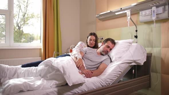 Sad Wife Stroking Sick Husband Lying in Hospital