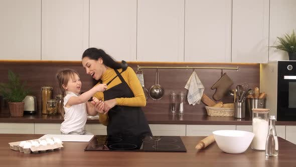 Mom and Little Daughter Singing in the Kitchen