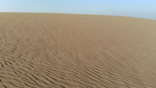 Parallel Sand Pattern Lines on Dune Surface in Desert