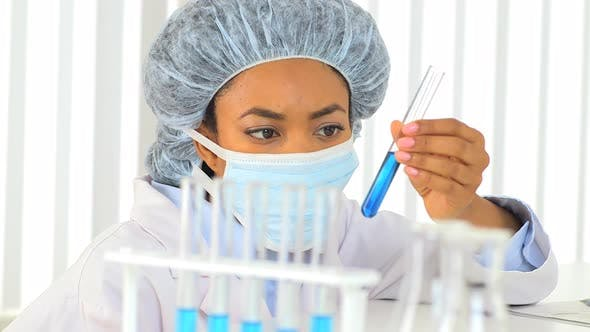 Thumbnail for Female African American scientist analyzing blue liquid in a test tube