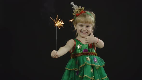 Happy Beautiful Baby Girl in Christmas Tree Costume. Burning Bengal Lights