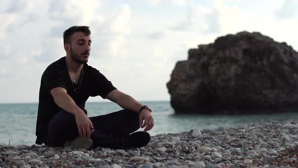 Thumbnail for Handsome Man Meditating on the Background of a Rock and the Sea