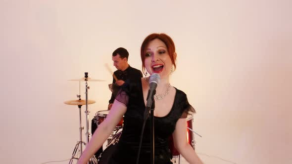 Cover Image for A Musical Band of Four People in Black Clothes Playing Song in the Studio - Filming a Dynamic Music