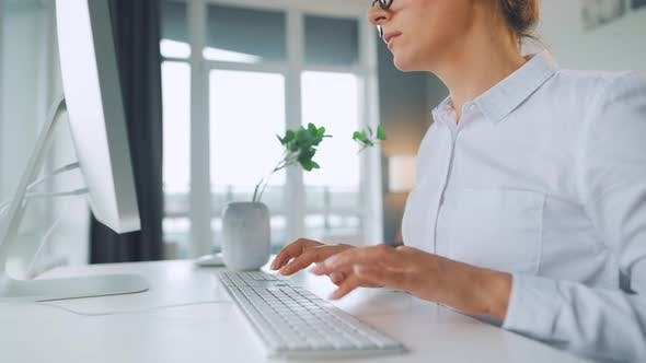 Thumbnail for Woman with Glasses Typing on a Computer Keyboard. Concept of Remote Work