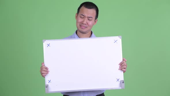 Thumbnail for Stressed Asian Businessman Holding White Board
