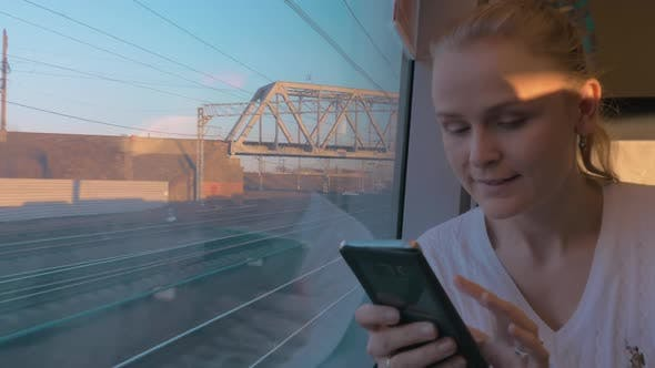 Thumbnail for Young Woman Rides a Train and Looking Out the Window