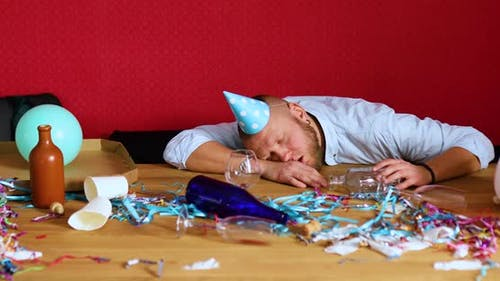 Bearded Man Sleeping at Table in Messy Room in Blue Cap After Bachelor or Birthday Party