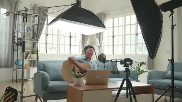 Asian Boy Playing Guitar And Sing A Song While Streaming. Professional Light Equipment
