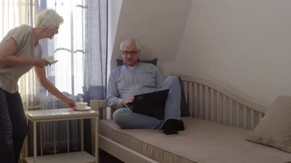 Thumbnail for Elderly Man Working on Laptop in Hotel and Wife Bringing Tea
