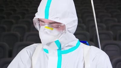 Male Cleaner in Antivirus Suit Disinfecting Cinema Hall