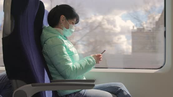 Frau trägt eine schützende medizinische Gesichtsmaske reitet in einem Zug