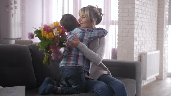 Thumbnail for Happy Mom Hugging Cute Son on Sofa at Mother's Day