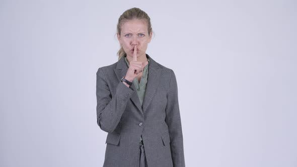Thumbnail for Young Stressed Blonde Businesswoman with Finger on Lips