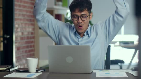 Asian creative happy arm raised while working on laptop.