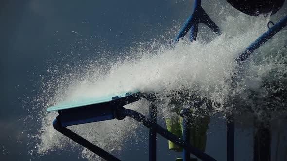 Cover Image for Vergnügungspark gegossen Wasser aus dem Eimer auf dem Hügel. Zeitlupe. Nahaufnahme