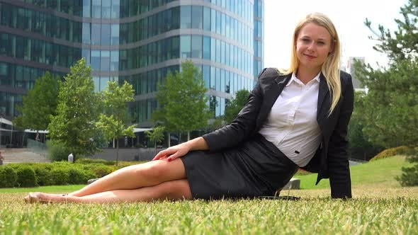 Thumbnail for A Young Beautiful Businesswoman Sits on Grass in a Park and Smiles at the Camera - Office Buildings