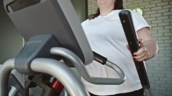 Thumbnail for Chubby Woman Using Elliptical Trainer
