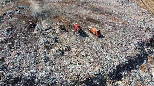 Aerial view of a garbage truck unloads a pile of garbage at a landfill.