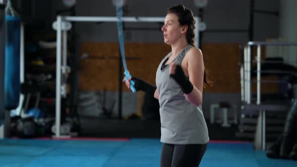 Female Boxer Jumping on Skipping Rope in Gym