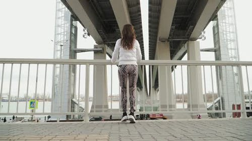 Young athletic girl in white jacket and leggings runs to the parapet and stopped.