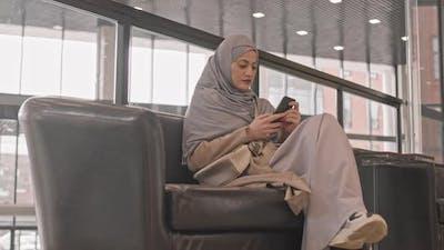 Arabic Woman Using Smartphone at Lounge