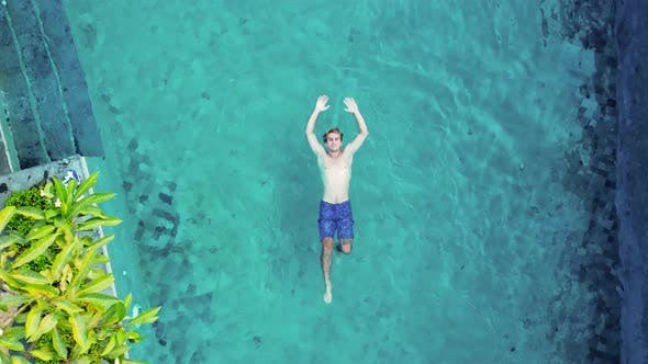Man in Blue Trunks Lays on the Blue Water Pool