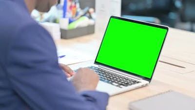 Rear View of Young Businessman Using Laptop with Chroma Screen