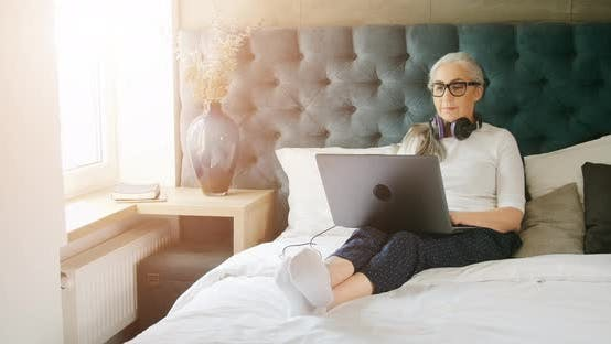 Thumbnail for Elderly Woman with Laptop in Bedroom