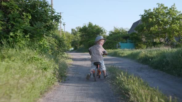 Thumbnail for Happy Childhood, Small Handsome Boy in Straw Hat Has Fun Cycling While Relaxing Outside City on