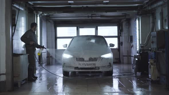 Thumbnail for Wide Shot of Worker Washing Vehicle in Car Wash. Caucasian Employee Using High-pressure Washer at